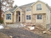 Custom home Essex County after completion of stucco front with stone and custom trim detail.