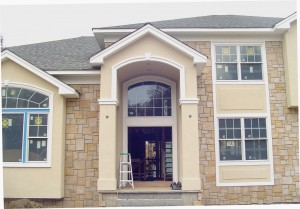 Custom column entrance with arched trim.  Raised stucco panel detail at windows.